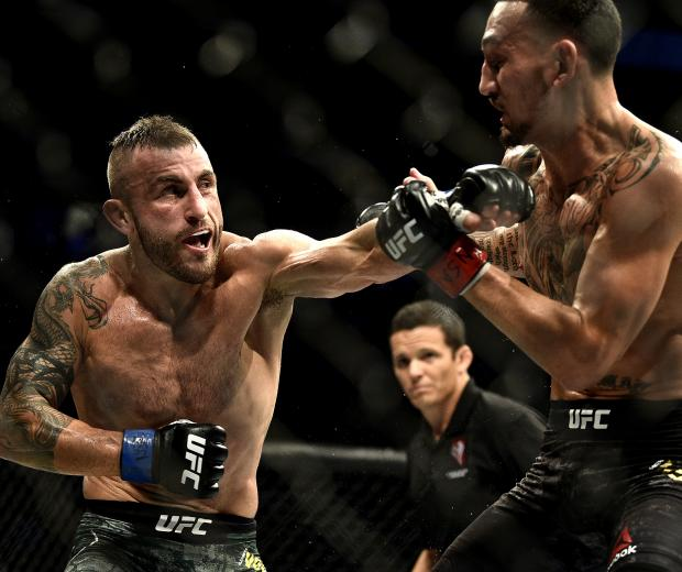 Alexander Volkanovski of Australia punches Max Holloway in their UFC featherweight championship bout during the UFC 245
