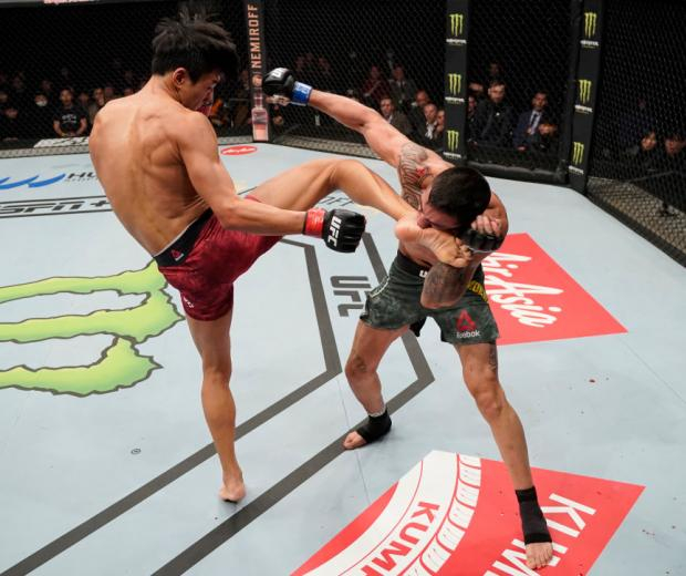 Seungwoo Choi of South Korea kicks Suman Mokhtarian of Australia in their featherweight fight during the UFC Fight Night