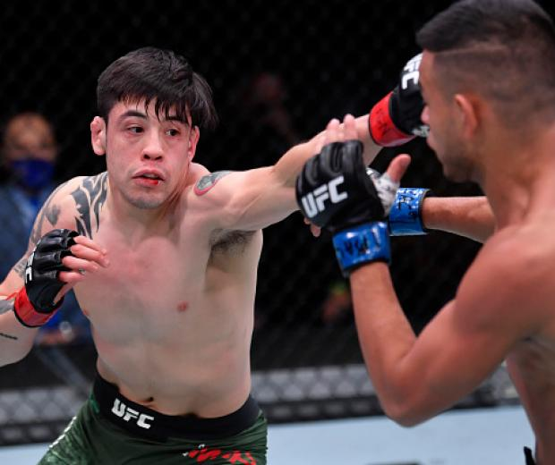Brandon Moreno of Mexico punches Brandon Royval in their flyweight bout during the UFC 255
