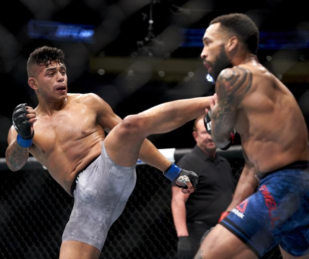 HOUSTON, TEXAS - FEBRUARY 08: (L-R) Jonathan Martinez kicks Andre Ewell in their bantyamweight bout during the UFC 247