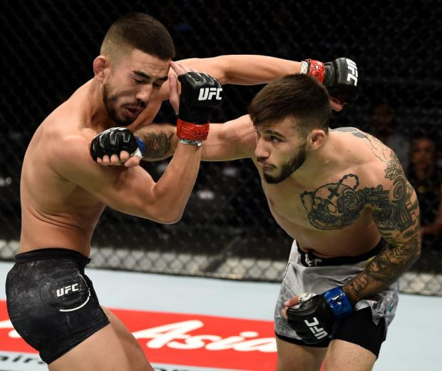 LAS VEGAS, NV - DECEMBER 30:  (R-L) Matheus Nicolau of Brazil punches Louis Smolka in their flyweight bout during the UFC 219 event inside T-Mobile Arena on December 30, 2017 in Las Vegas, Nevada. (Photo by Jeff Bottari/Zuffa LLC/Zuffa LLC via Getty Image