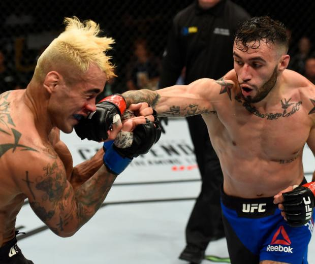 UNIONDALE, NY - JULY 22:  (R-L) Shane Burgos punches Godofredo Pepey of Brazil in their featherweight bout during the UFC Fight Night event inside the Nassau Veterans Memorial Coliseum on July 22, 2017 in Uniondale, New York. (Photo by Josh Hedges/Zuffa L