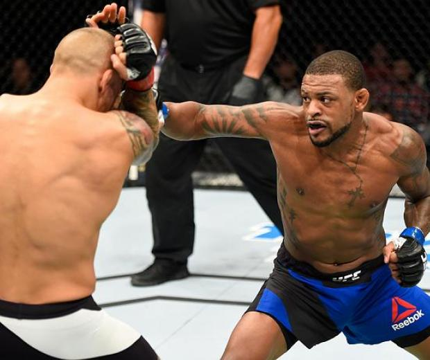 HIDALGO, TX - SEPTEMBER 17:   (R-L) Michael Johnson punches Dustin Poirier in their lightweight bout during the UFC Fight Night event at State Farm Arena on September 17, 2016 in Hidalgo, Texas. (Photo by Josh Hedges/Zuffa LLC/Zuffa LLC via Getty Images)