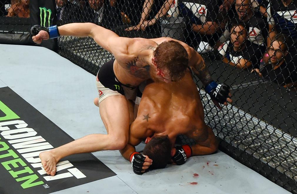 LAS VEGAS, NV - JULY 11: Conor McGregor (top) punches Chad Mendes in their UFC interim featherweight title fight during the UFC 189 event inside MGM Grand Garden Arena on July 11, 2015 in Las Vegas, Nevada. (Photo by Josh Hedges/Zuffa LLC/Zuffa LLC via Getty Images)