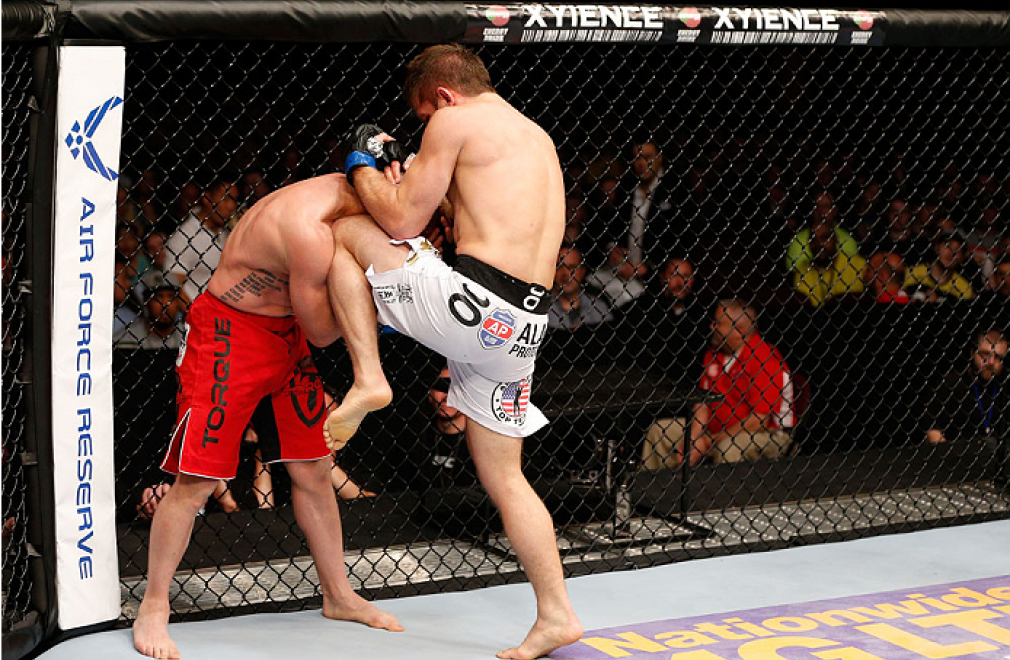 CINCINNATI, OH - MAY 10:  (R-L) Nik Lentz knees Manny Gamburyan in their featherweight fight during the UFC Fight Night event at the U.S. Bank Arena on May 10, 2014 in Cincinnati, Ohio. (Photo by Josh Hedges/Zuffa LLC/Zuffa LLC via Getty Images)