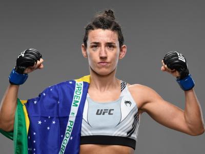 Marina Rodriguez posa com os braços flexionados e com a bandeira do Brasil sobre o ombro direito após a vitória sobre Mackenzie Dern no UFC Vegas 39