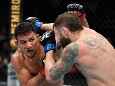 RALEIGH, NORTH CAROLINA - JANUARY 25: (L-R) Rafael Dos Anjos of Brazil punches Michael Chiesa in their welterweight fight during the UFC Fight Night
