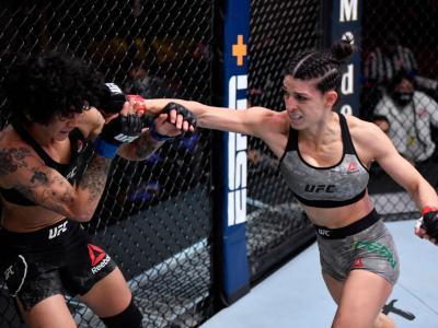 LAS VEGAS, NEVADA - DECEMBER 12: (R-L) Mackenzie Dern punches Virna Jandiroba of Brazil in their women's strawweight bout during the UFC 256