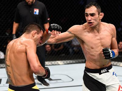 MEXICO CITY, MEXICO - NOVEMBER 05: (R-L) Tony Ferguson of the United States punches Rafael Dos Anjos of Brazil in their lightweight bout during the UFC Fight Night