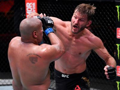 LAS VEGAS, NEVADA - AUGUST 15: In this handout image provided by UFC, Stipe Miocic (R) punches Daniel Cormier in their UFC heavyweight championship bout during the UFC 252