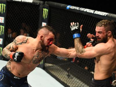 WINNIPEG, CANADA - DECEMBER 16: (L-R) Santiago Ponzinibbio of Argentina punches Mike Perry in their welterweight bout during the UFC Fight Night event