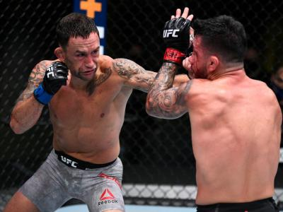 LAS VEGAS, NEVADA - AUGUST 22: In this handout image provided by UFC, (L-R) Frankie Edgar punches Pedro Munhoz of Brazil in their bantamweight fight during the UFC Fight Night
