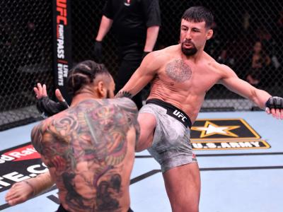 LAS VEGAS, NEVADA - FEBRUARY 13: (R-L) Chris Gutierrez kicks Andre Ewell in their 140-pound catchweight fight during the UFC 258