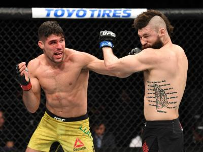 PHOENIX, ARIZONA - FEBRUARY 17: (L-R) Vicente Luque punches Bryan Barberena in their welterweight bout during the UFC Fight Night