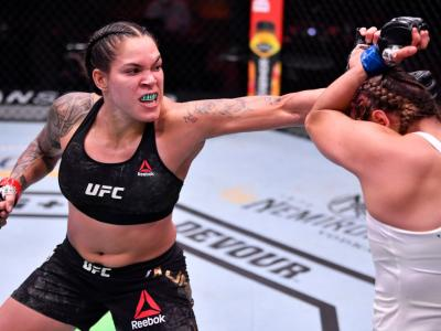 LAS VEGAS, NEVADA - JUNE 06: In this handout provided by UFC, (L-R) Amanda Nunes of Brazil punches Felicia Spencer of Canada in their UFC featherweight championship bout during the UFC 250