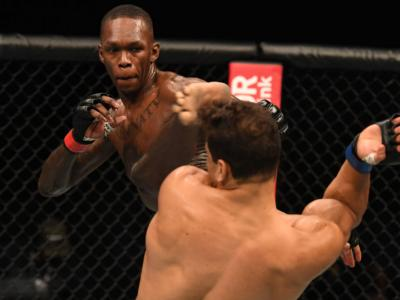 ABU DHABI, UNITED ARAB EMIRATES - SEPTEMBER 27: (L-R) Israel Adesanya of Nigeria lands a head kick to Paulo Costa of Brazil in their middleweight championship bout during UFC 253