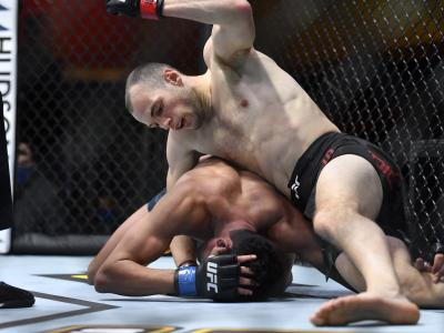 LAS VEGAS, NEVADA - MARCH 06: (R-L) Uros Medic of Serbia punches Aalon Cruz in their lightweight fight during the UFC 259