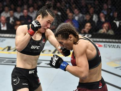 LAS VEGAS, NEVADA - MARCH 07: (L-R) Zhang Weili of China kicks Joanna Jedrzejczyk of Poland in their UFC strawweight championship fight during the UFC 248