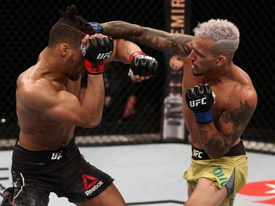 BRASILIA, BRAZIL - MARCH 14: Charles Oliveira of Brazil punches Kevin Lee in their lightweight fight during the UFC Fight Night