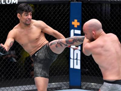 LAS VEGAS, NEVADA - DECEMBER 05: (L-R) Gabriel Benitez of Mexico kicks Justin Jaynes in a lightweight bout during the UFC Fight Night event at UFC APEX