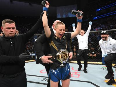 JACKSONVILLE, FLORIDA - APRIL 24: Rose Namajunas reacts after defeating Zhang Weili of China in their UFC women's strawweight championship bout as UFC President Dana White places the championship belt on her during the UFC 261