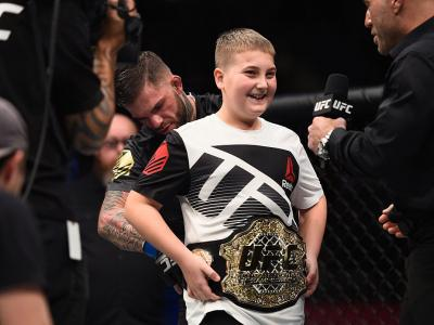 LAS VEGAS, NV - DECEMBER 30: Cody Garbrandt (back) places the UFC title belt around a young fan's wasit after defeating Dominick Cruz in their UFC bantamweight championship bout during the UFC 207 event at T-Mobile Arena on December 30, 2016 in Las Vegas,