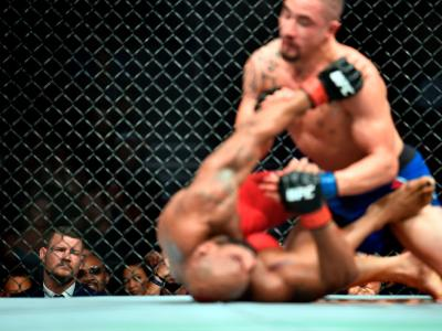LAS VEGAS, NV - JULY 08:  UFC Middleweight Champion Michael Bisping of England (L) watches as Yoel Romero of Cuba and Robert Whittaker of New Zealand exchange punches in their interim UFC middleweight championship bout during the UFC 213 event at the T-Mo