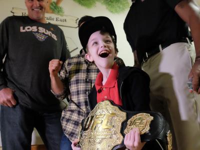 A children from Ryan House in Phoenix holds a UFC belt (Photo credit Juan Cardenas)