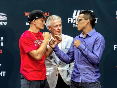 SASKATOON, SK - JUNE 24:  Max Holloway (L) and Charles Oliveira (R) square off in front of join Tom Wright, UFC Executive Vice-President and General Manager for Canada, Australia and New Zealand, at a press conference at the SaskTel Centre, June 24,  2015
