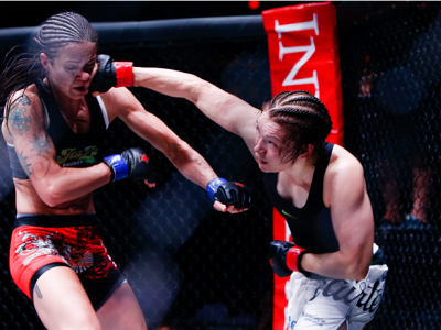 Katja Kankaanpaa punches Stephanie Eggink during their strawweight title fight during Invicta FC 8.