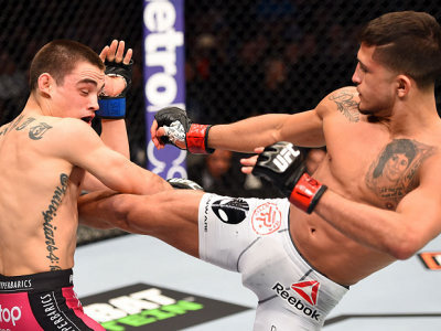 DALLAS, TX - MARCH 14:  (R-L) Sergio Pettis lands a kick to the body of Ryan Benoit in their flyweight bout during the UFC 185 event at the American Airlines Center on March 14, 2015 in Dallas, Texas. (Photo by Josh Hedges/Zuffa LLC/Zuffa LLC via Getty Im