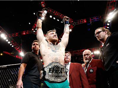 LAS VEGAS, NV - DECEMBER 12:  Conor McGregor of Ireland exits the Octagon after his victory over Jose Aldo of Brazil in their UFC featherweight championship bout during the UFC 194 event inside MGM Grand Garden Arena on December 12, 2015 in Las Vegas, Nev