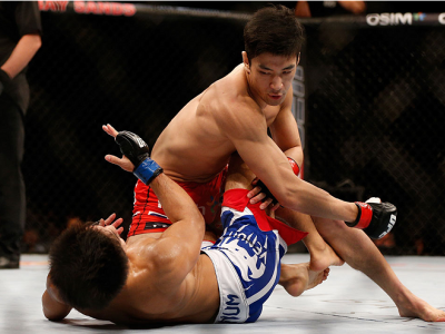 SINGAPORE - JANUARY 04:  (R-L) Kang Kyung Ho punches Shunichi Shimizu in their bantamweight bout during the UFC Fight Night event at the Marina Bay Sands Resort on January 4, 2014 in Singapore. (Photo by Josh Hedges/Zuffa LLC/Zuffa LLC via Getty Images)
